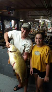 Amelia Whalen stands with her father who holds the record-breaking fish.