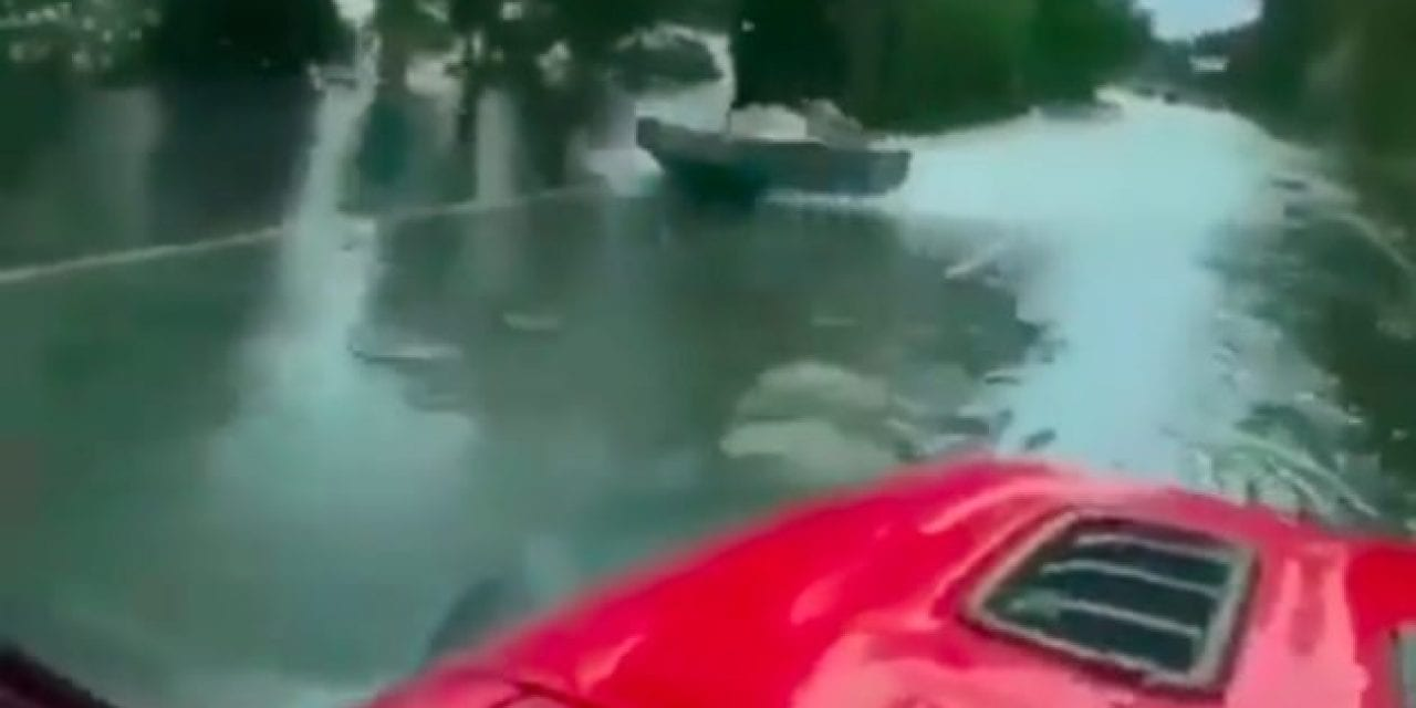 Driver Passes Quick-Moving Jet Boat on a Flooded Highway