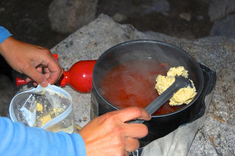 Putting corn dumpling batter on top of salsa soup
