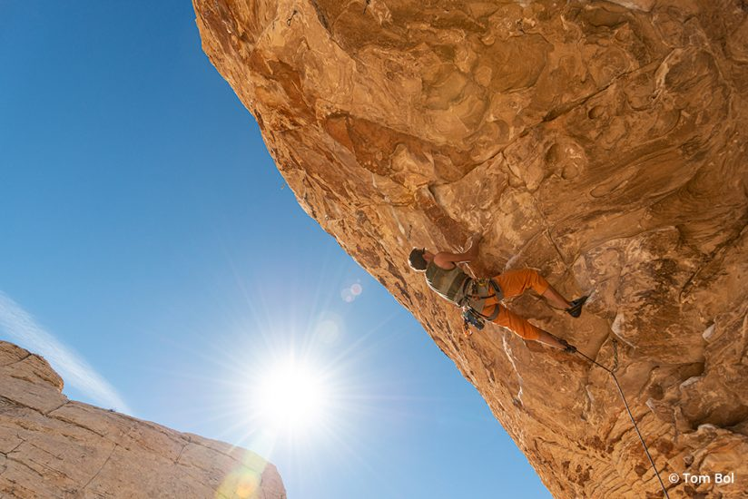 adventure sports photography image of rock climber ascending a steep roof